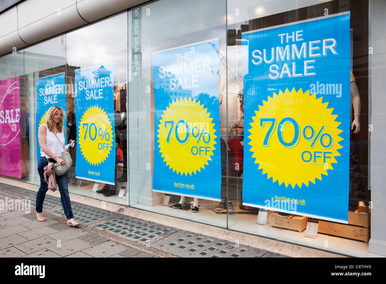 Woman walks past 70 per cent reduction summer sales posters of a Burton's or Dorothy Perkins Shop in New Oxford - Stock Image