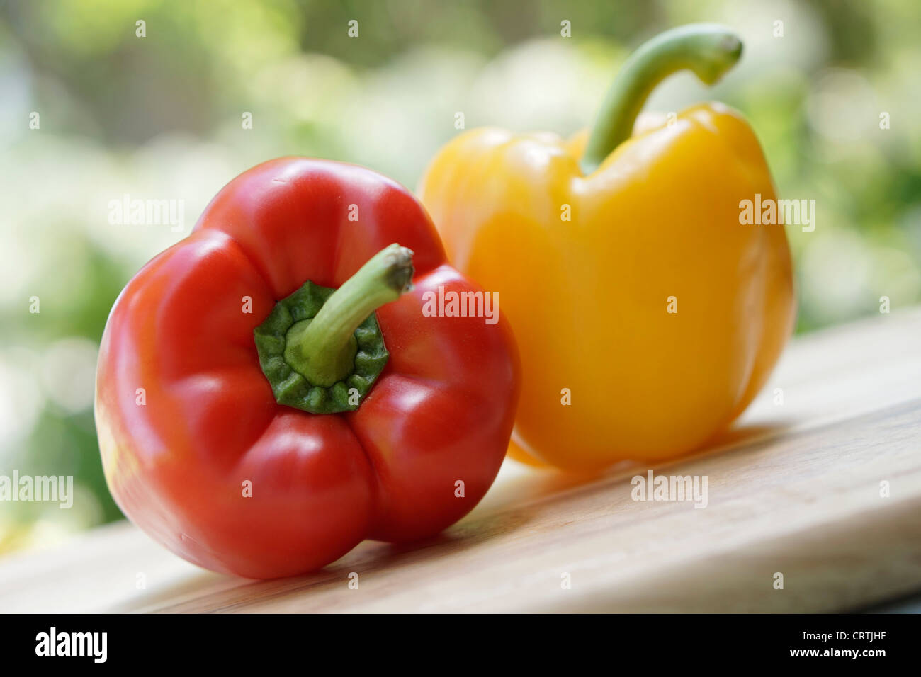 Peppers, Red and Yellow Bell Pepper on cutting board - Stock Image
