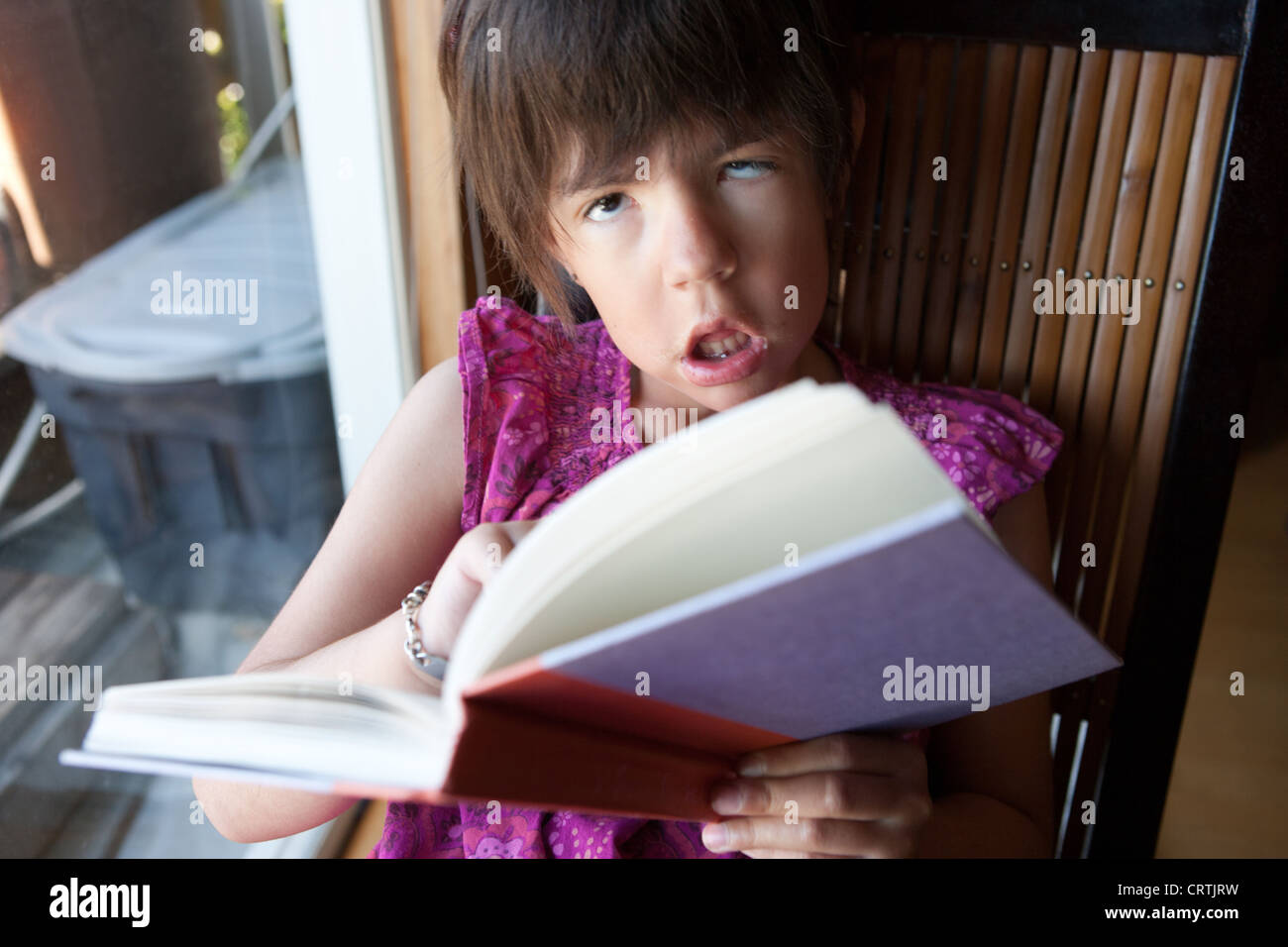 An eight year old girl with myotonic muscular dystrophy holding a book in her hand and asking about the meaning - Stock Image
