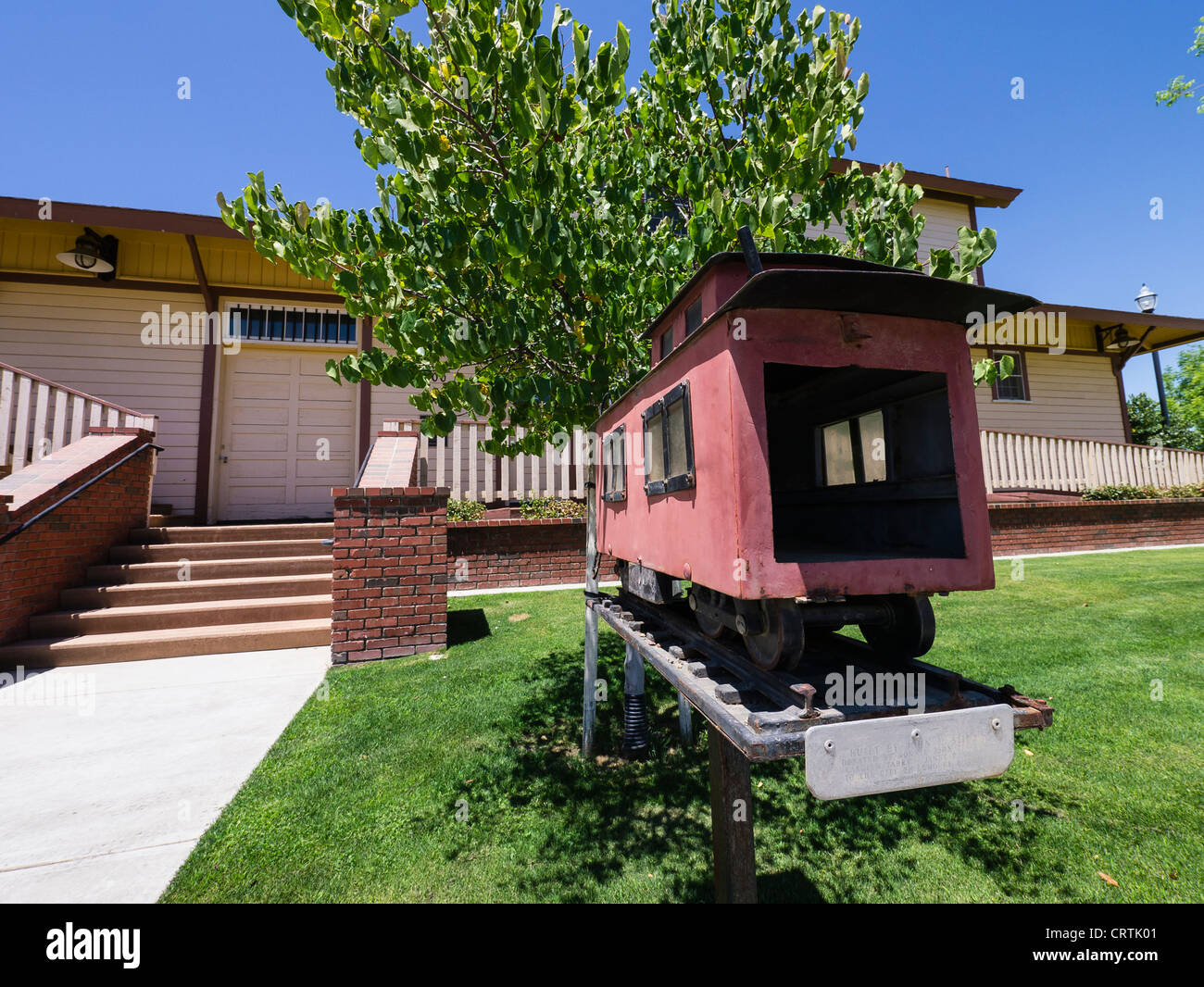 A little red model caboose serves as the mailbox for the historic train station in Lemoore, California, USA. - Stock Image