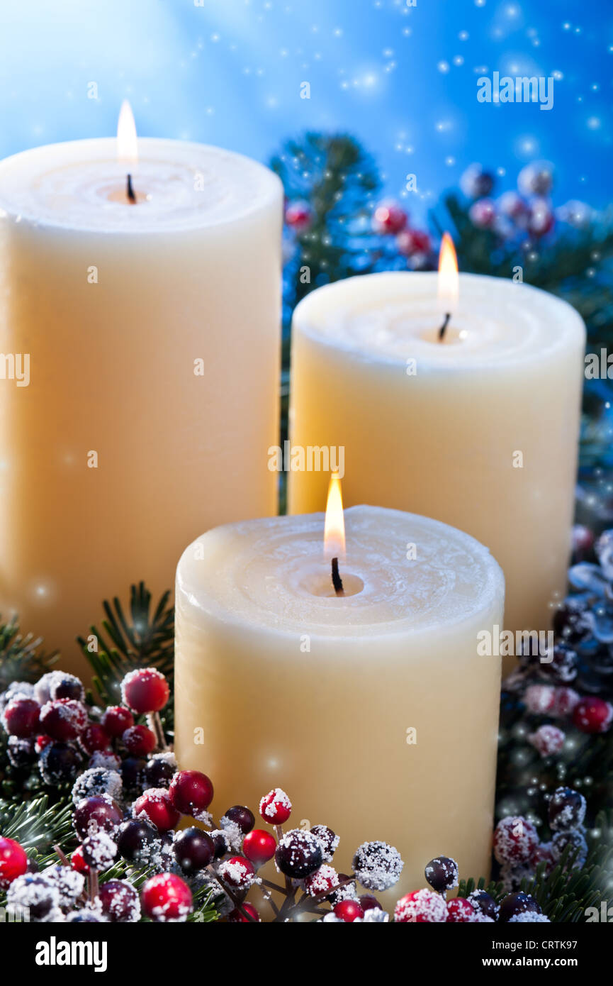 Three candles in an advent flower arrangement for advent and Christmas with snow fall Stock Photo