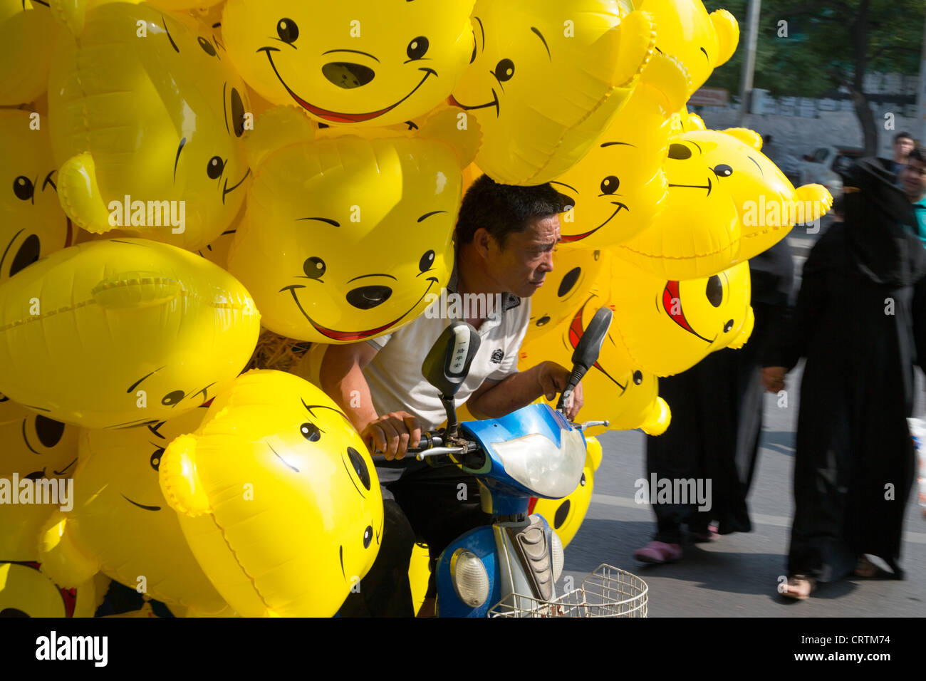 Man with Winnie The Pooh balloons, in the Sanlitun upmarket shopping district, in Beijing, China. - Stock Image