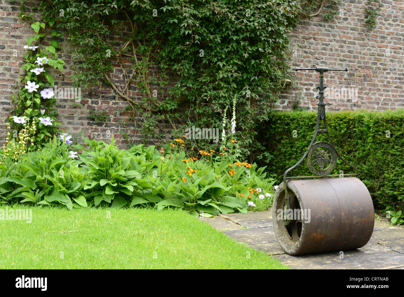 lawn roller in walled garden - Stock Image