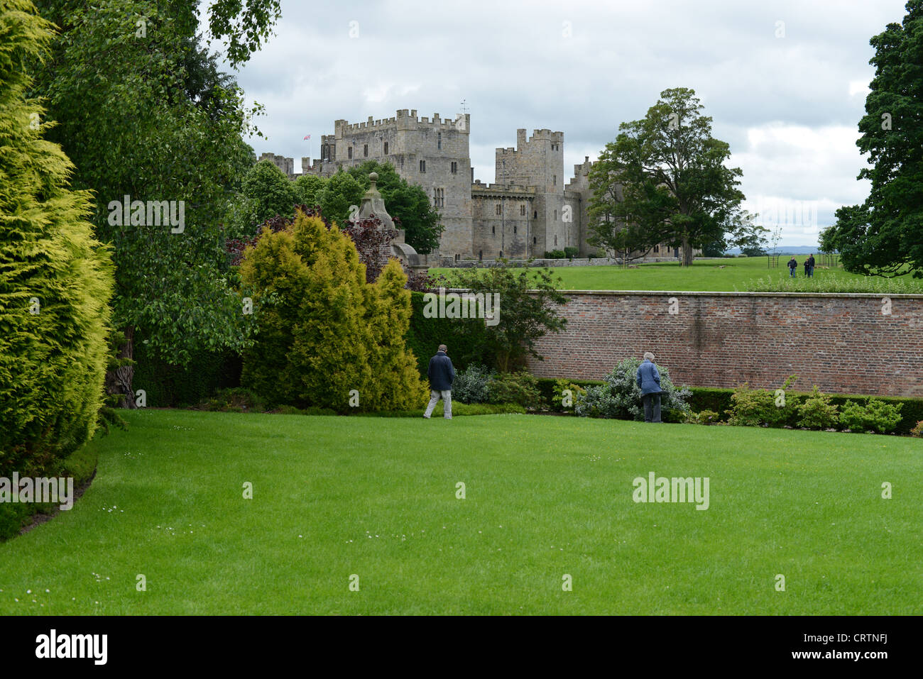 Tourists wander around the gardens at Raby Castle, County Durham, UK - Stock Image