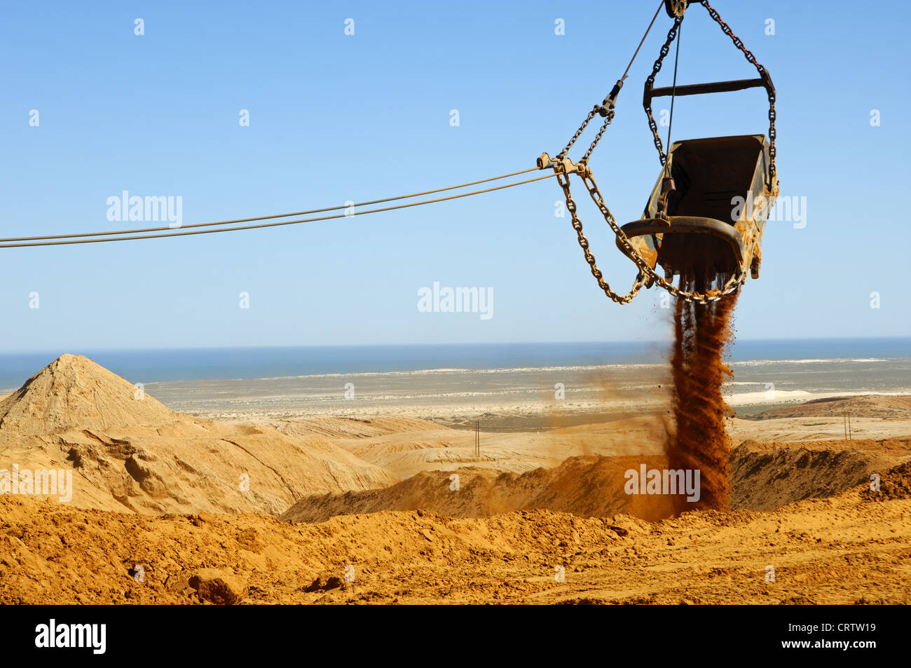 Bucket of a dragline excavator dumping earth Stock Photo