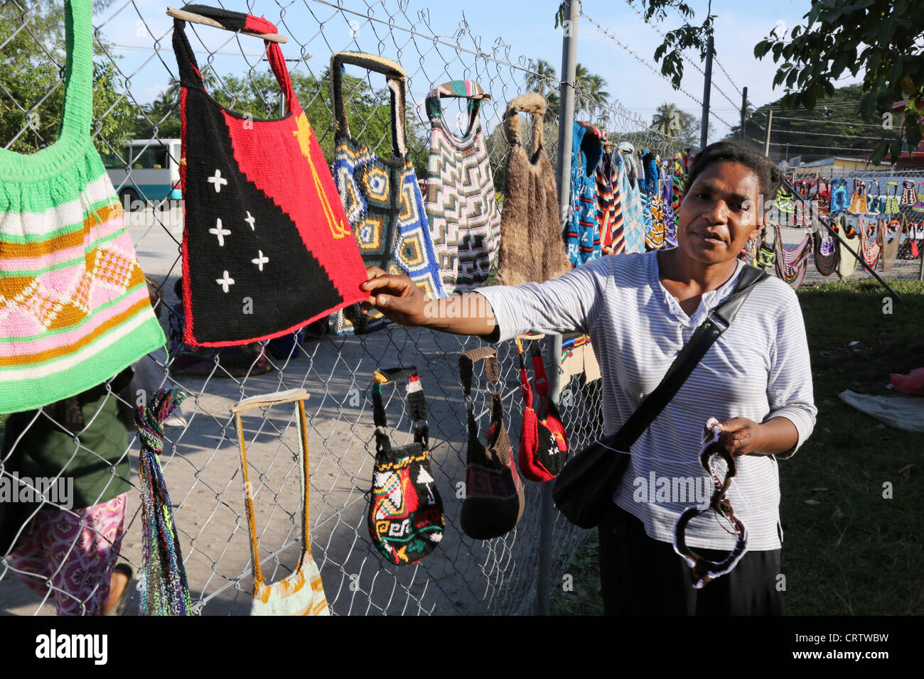 Trader offers traditionally bilum nets at a market in Madang, Papua New Guinea - Stock Image