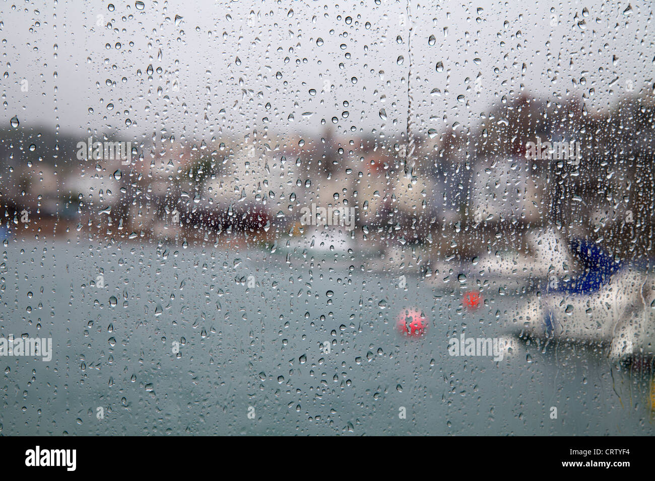 Rain drops on the windows of the ferry to Herm overlooking St Peter Port harbour, Guernsey - Stock Image