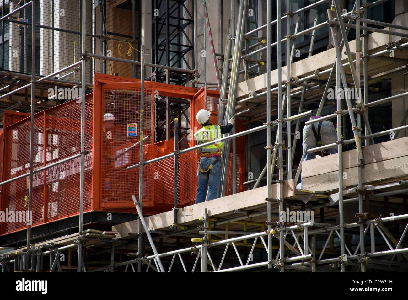 Construction workers on scaffolding in City of London - Stock Image