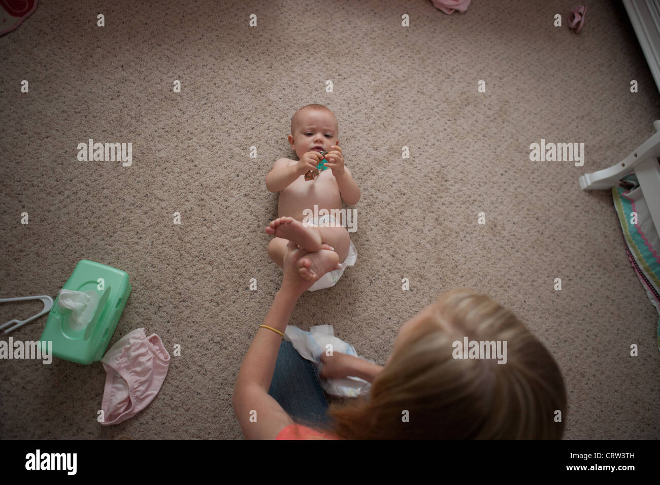Older sister changing diaper for ten month old sister at home. - Stock Image