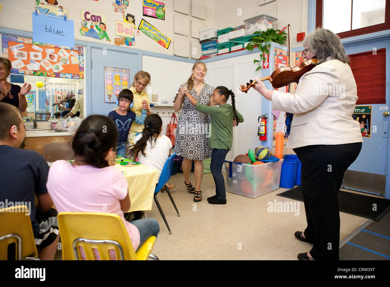 Celebration in a special education classroom, USA, teachers play music and dance with students. - Stock Image