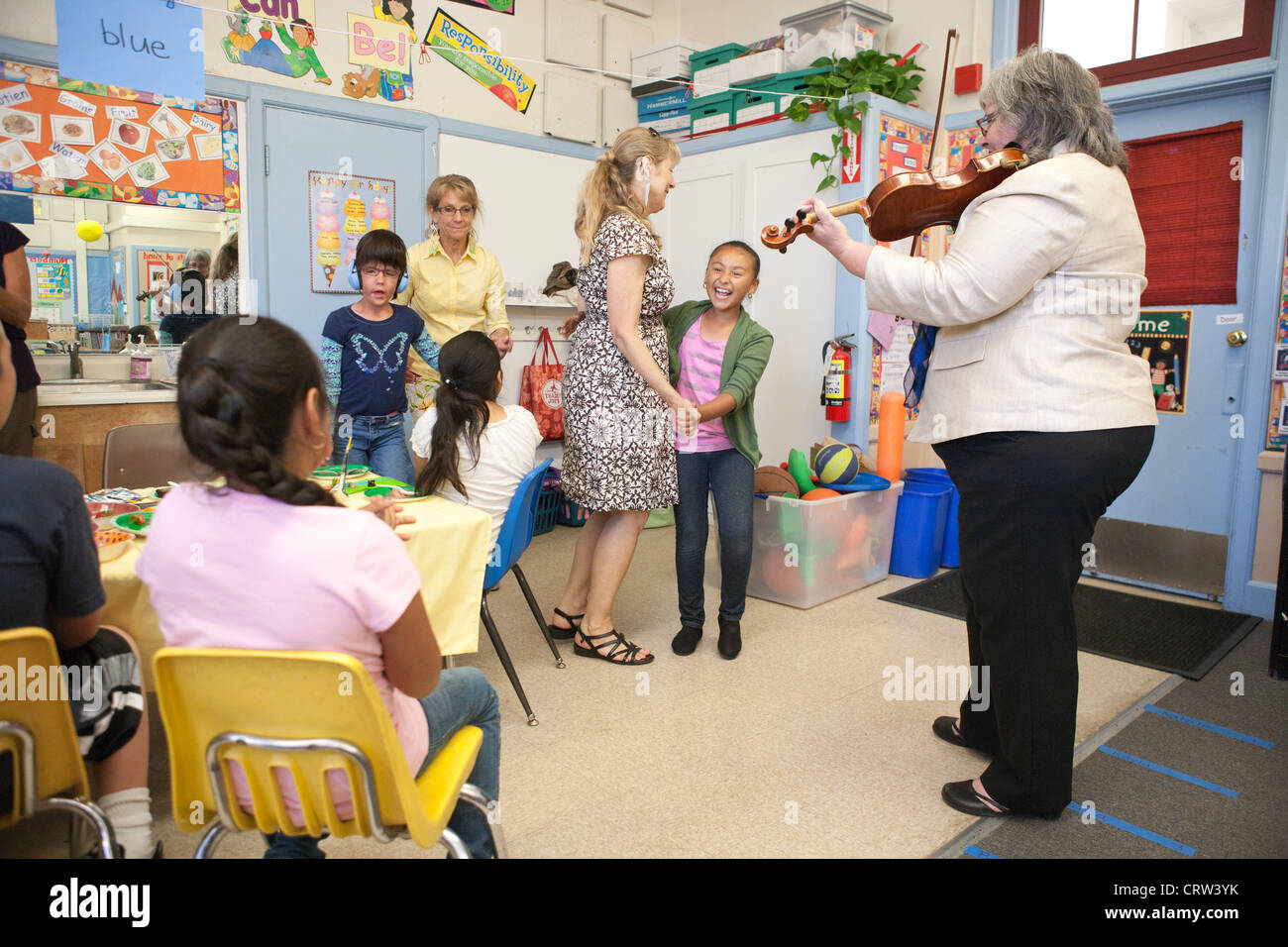 Celebration of last day of school in special education classroom, mixed age ability levels.  Teachers play music - Stock Image