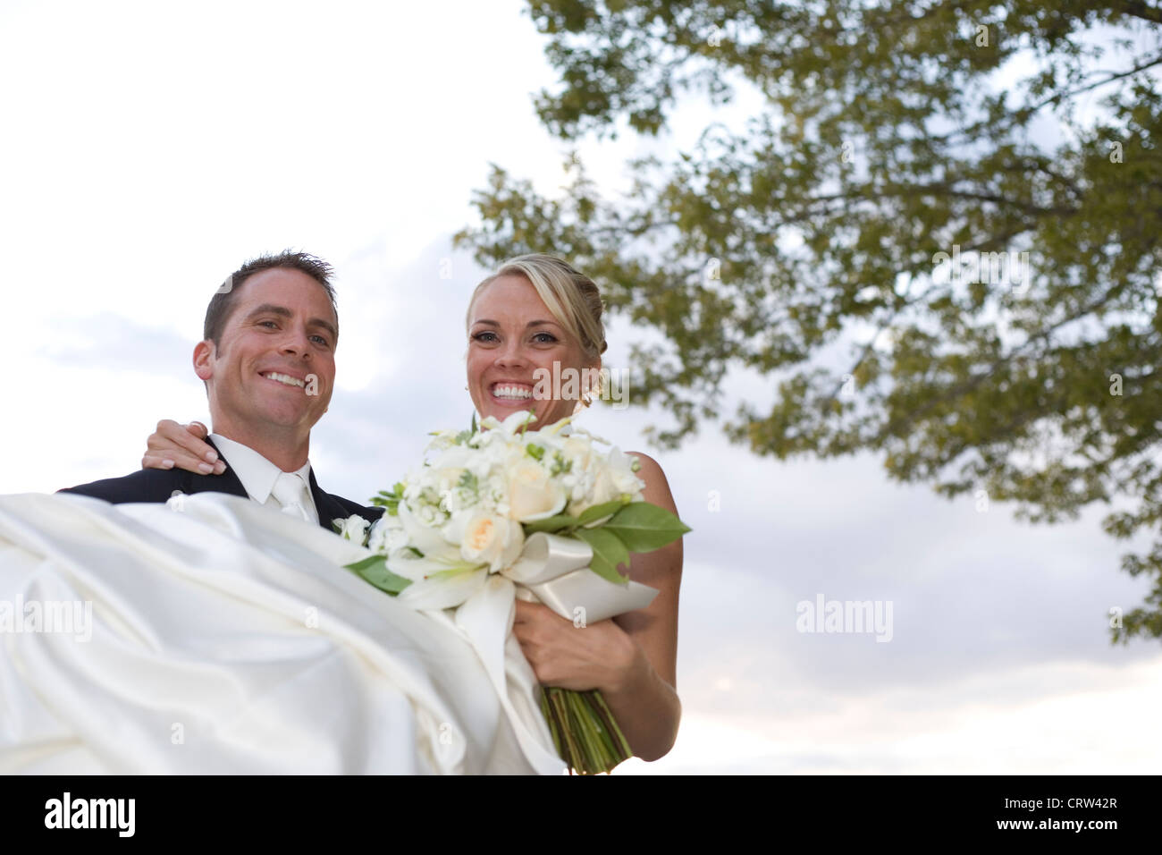 Groom holds bride outdoors just after wedding ceremony. - Stock Image