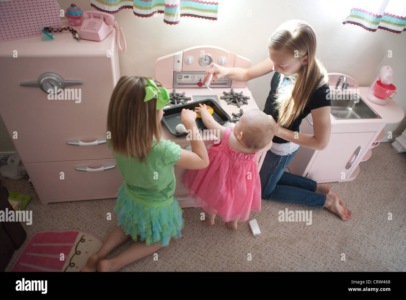 Two older sisters playing with one year old sibling in ...