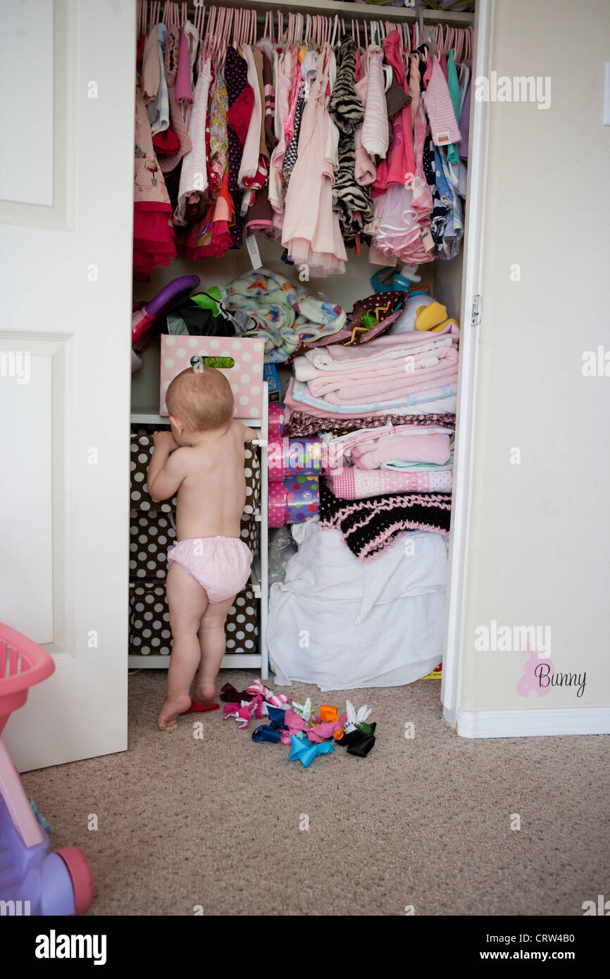 One year old girl looks for her toys in her bedroom closet. - Stock Image
