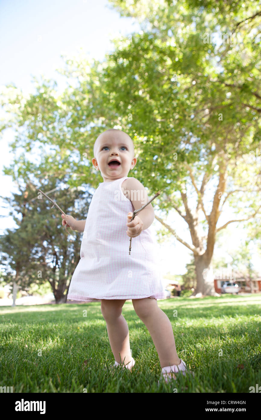 A happy one year old girl looks up, holding sticks in her hands in a park. - Stock Image