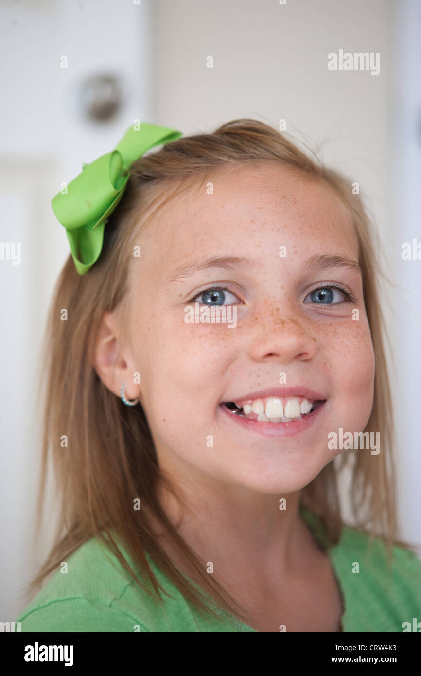 Happy nine year old girl swmiling wearing a green ribbon. - Stock Image