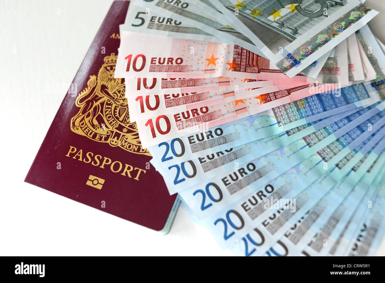 Selection of Euro currency notes in 5s 10s and 20s and a British passport - Stock Image