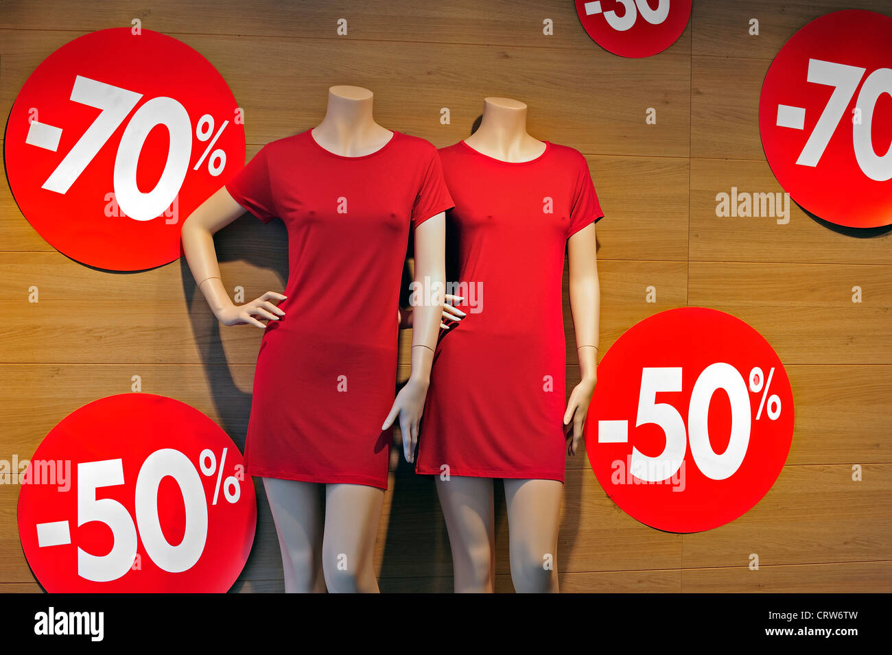 Discount notices showing deductions in shop window of clothes store during the summer sales in shopping street - Stock Image