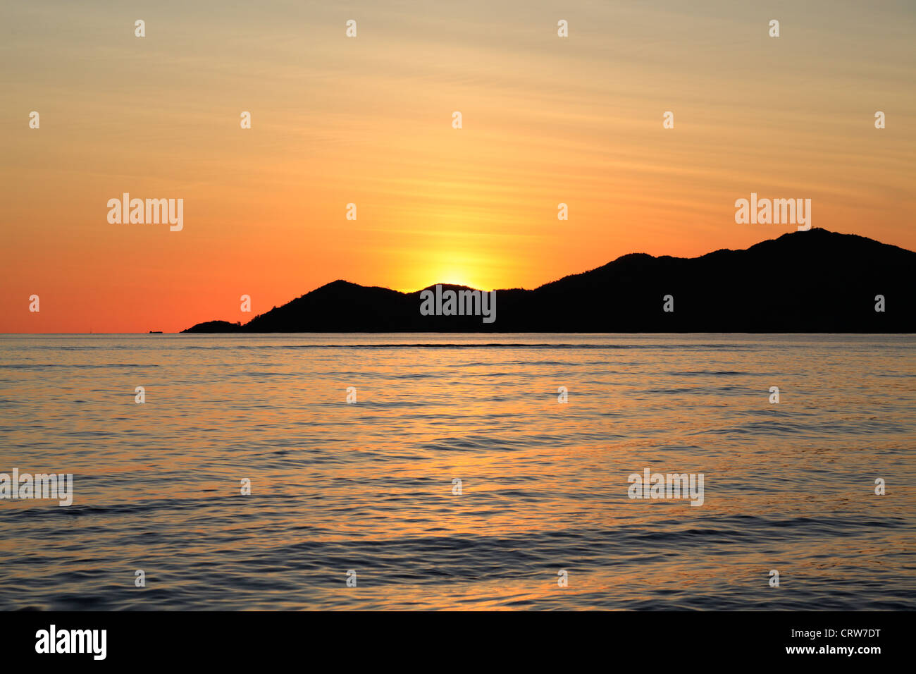 Sun sets behind the island of Praslin as seen from La Digue in the Seychelles - Stock Image