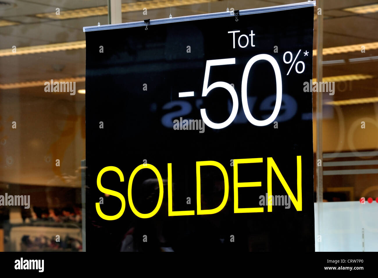 Discount notice showing deductions in shop window of store during the summer sales in shopping street, Ghent, Belgium - Stock Image