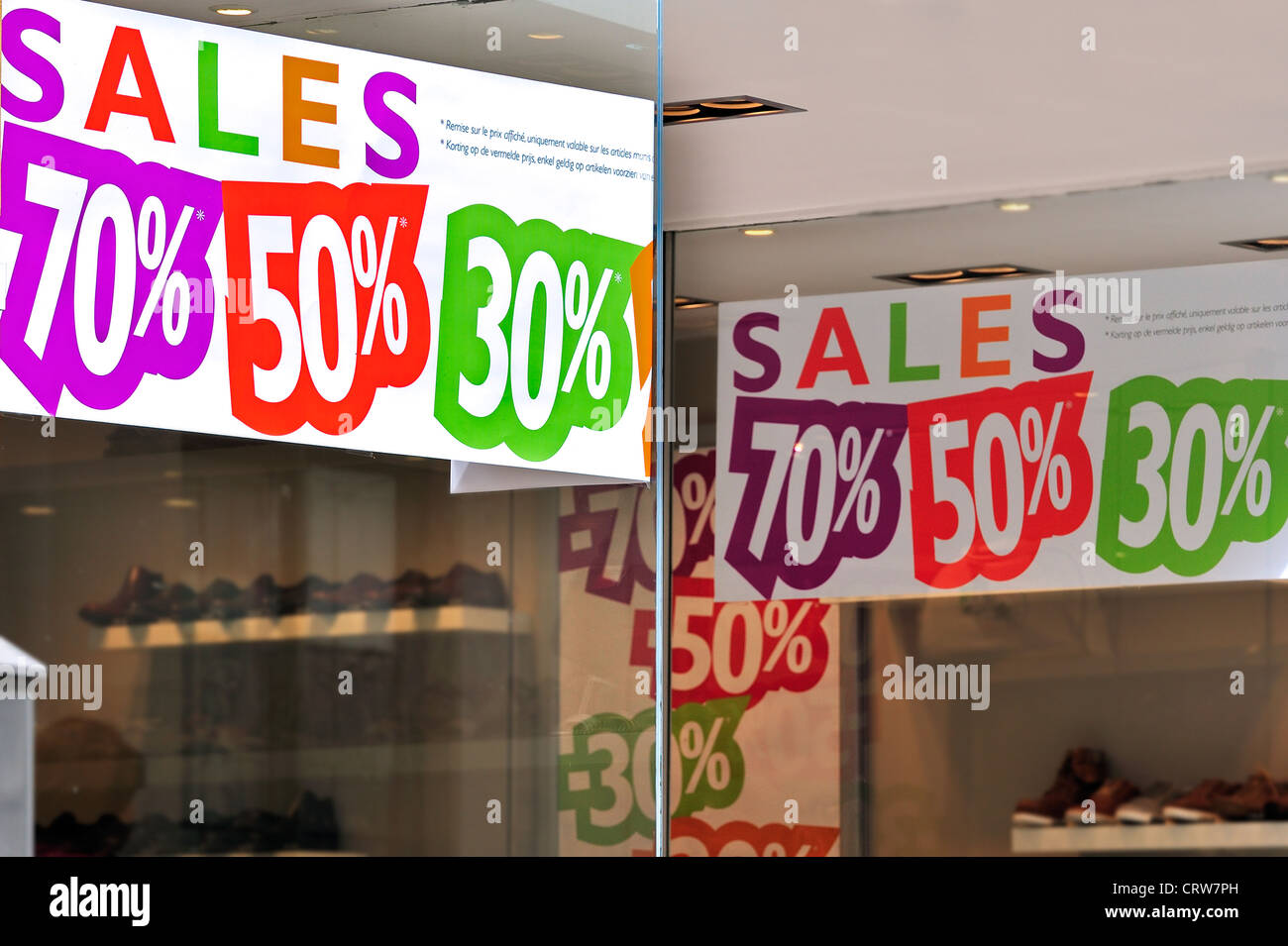 Shoes and discount signs showing deductions in shop window of shoe store during the summer sales in shopping street - Stock Image