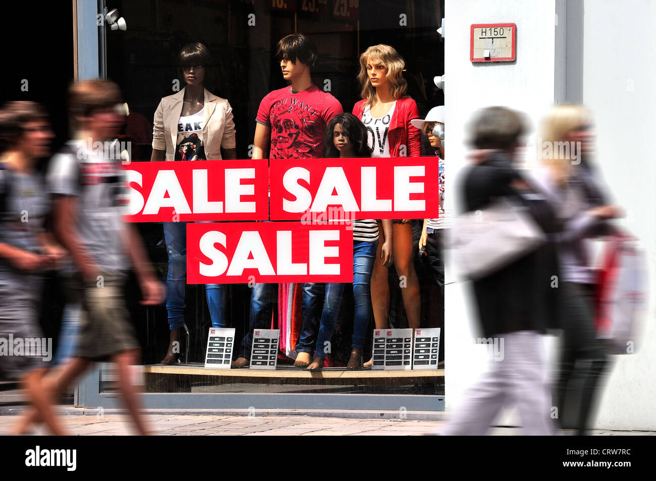 Mannequins and discount signs showing deductions in shop window of clothes store during the summer sales in shopping - Stock Image