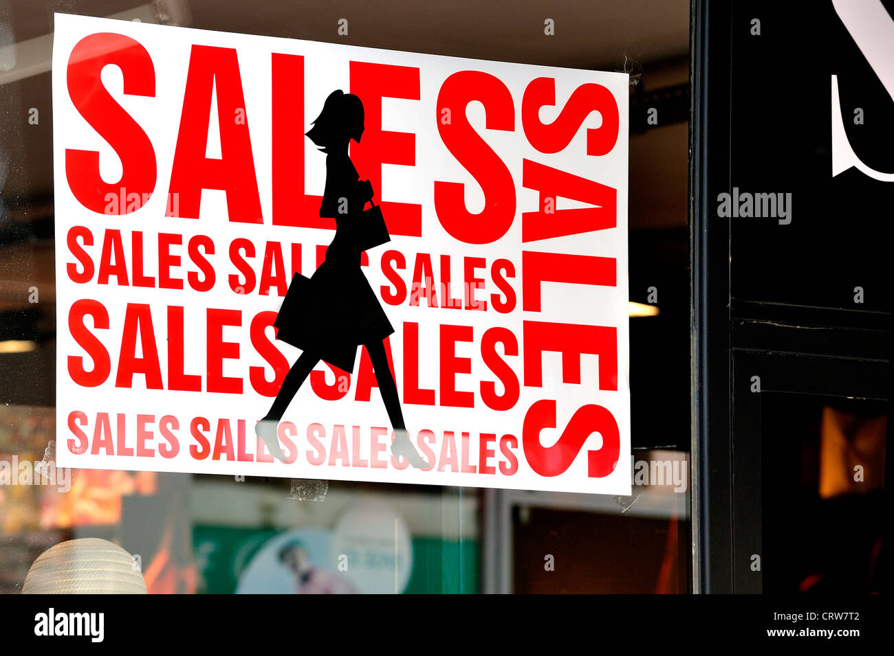 Discount sign showing deductions in shop window of store during the summer sales in shopping street - Stock Image