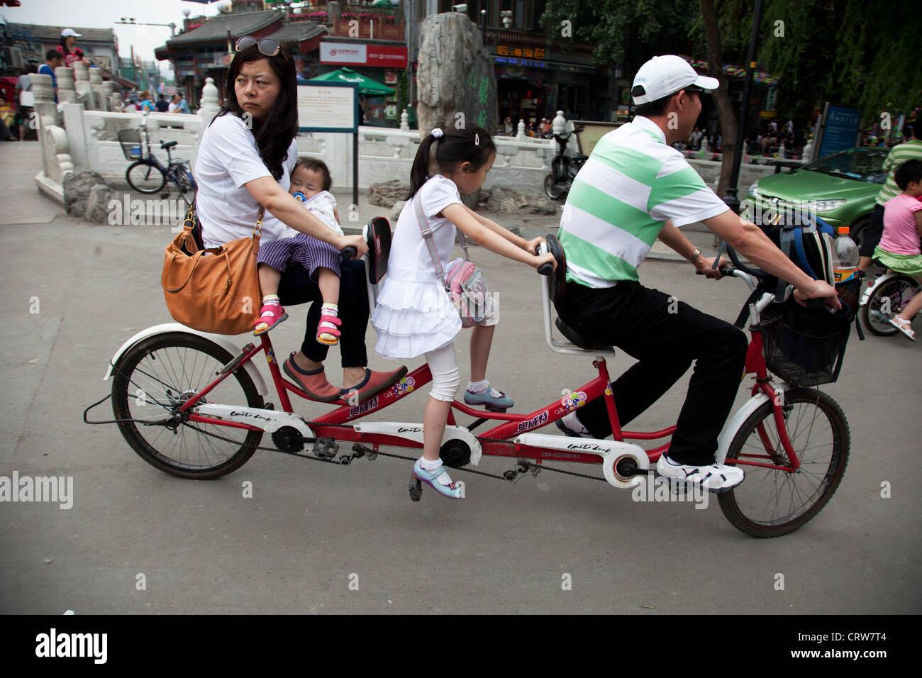 Family riding along on a triple tandem bicycle in Shichahai area, near to Yandai Xiejie and Yinding Bridge, Beijing, - Stock Image
