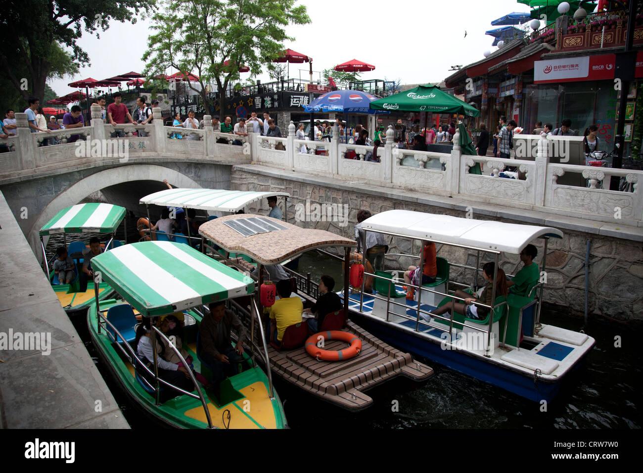 Small boats create a waterway traffic jam on Shichahai lake at Yinding bridge Beijing, China. - Stock Image