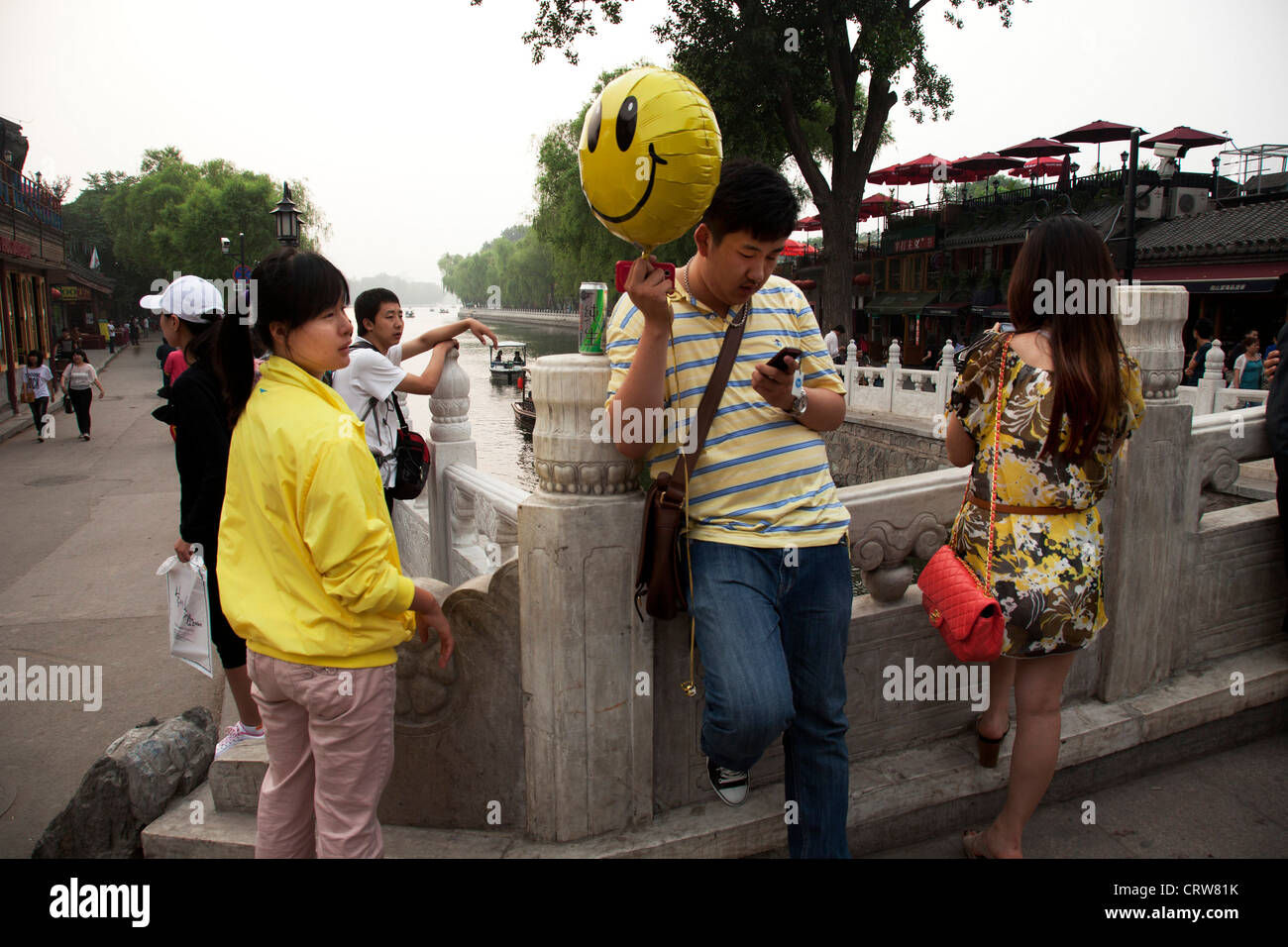 Standing on Yinding bridge holding a yellow smiley face balloon. Shichahai dates back to the Jin Dynasty. - Stock Image