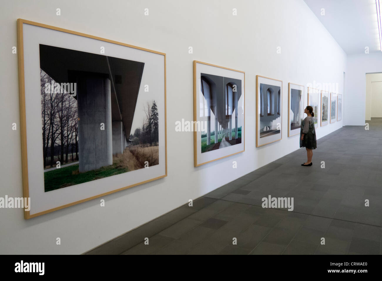 Woman looking at photographs at Kuppersmuhle Museum in Duisburg Germany - Stock Image