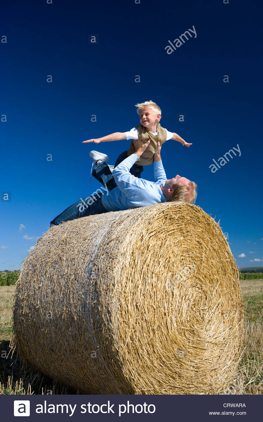 Father playing with son (7-9) on hay bale, low angle view - Stock Image