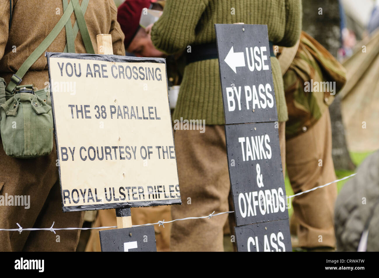 Signs from a WW2 reenactment group 'You are crossing the 38 parallel by courtesy of the Royal Ulster Rifles' - Stock Image