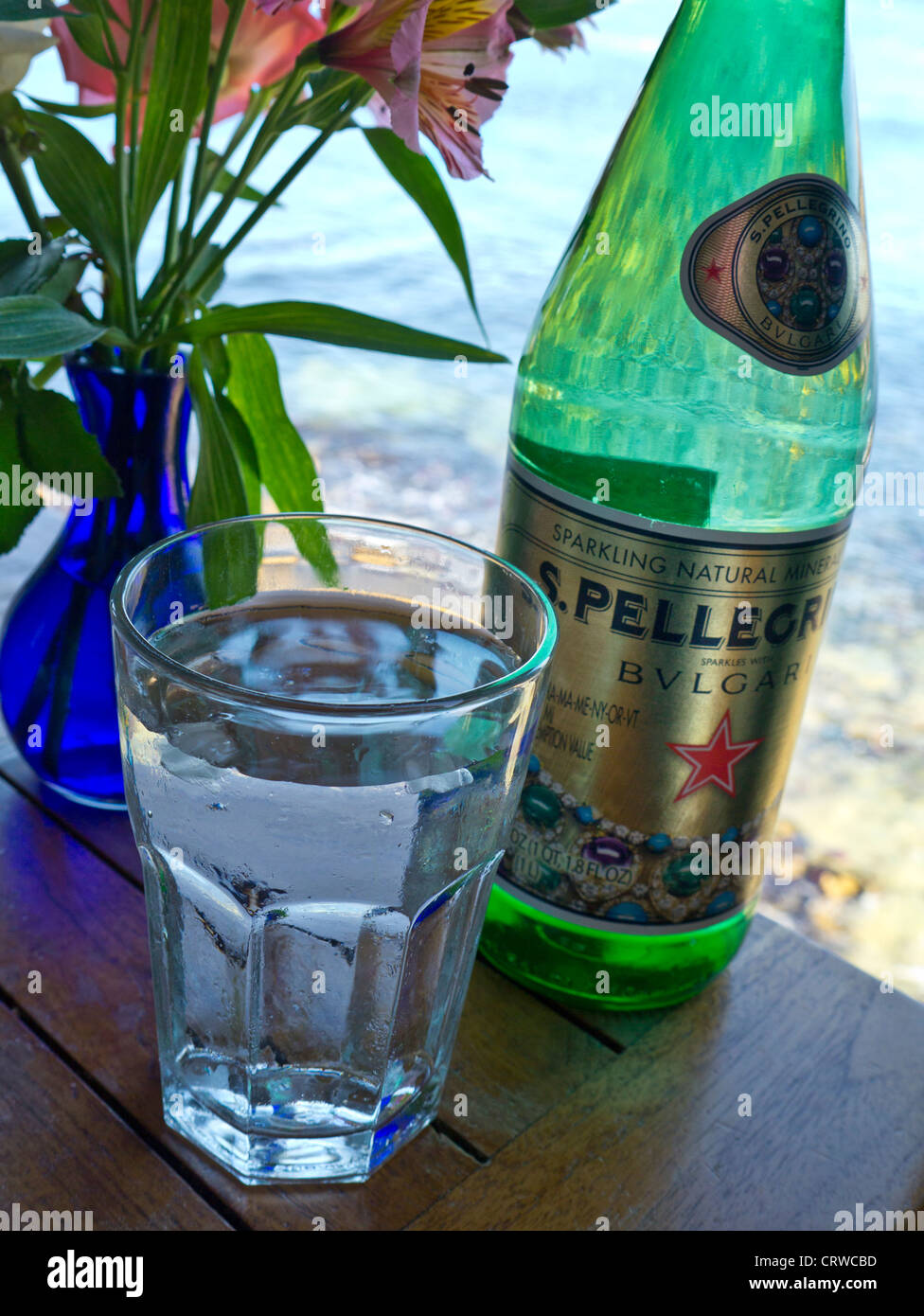 Pellegrino Bulgari luxury bottled water and glass on floral restaurant table with sea view - Stock Image