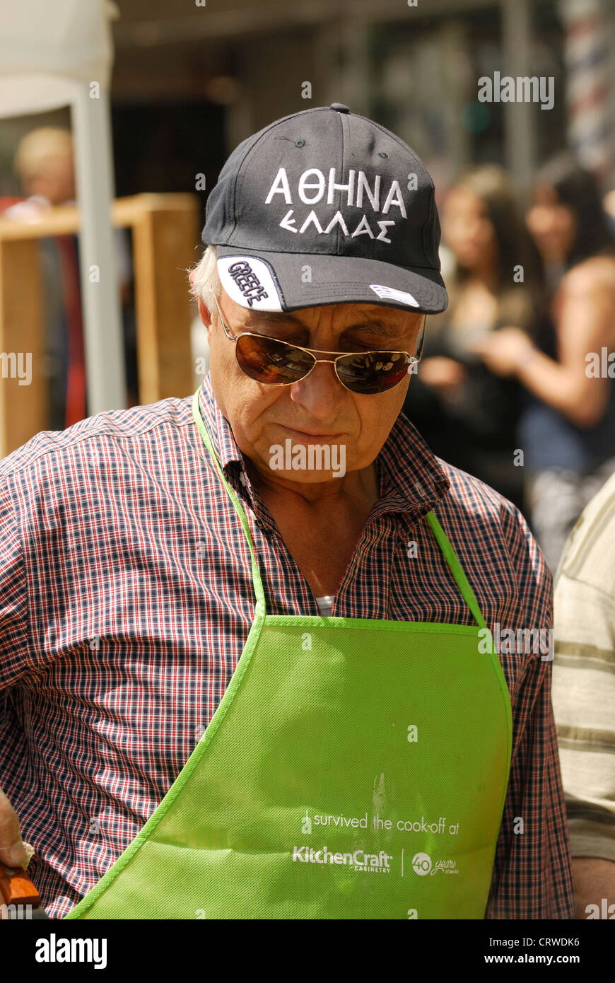 Man wearing an apron and a cap with Greek language on it during Greek Day Vancouver - Stock Image