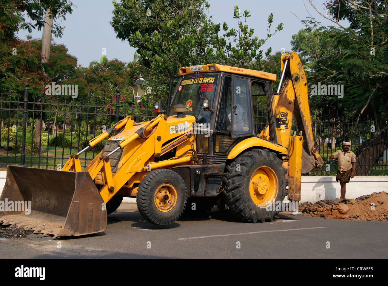 JCB Earth mover Digging the Tarred Road for underlying Pipe Maintenance Work at Pondicherry (Puducherry) in India - Stock Image