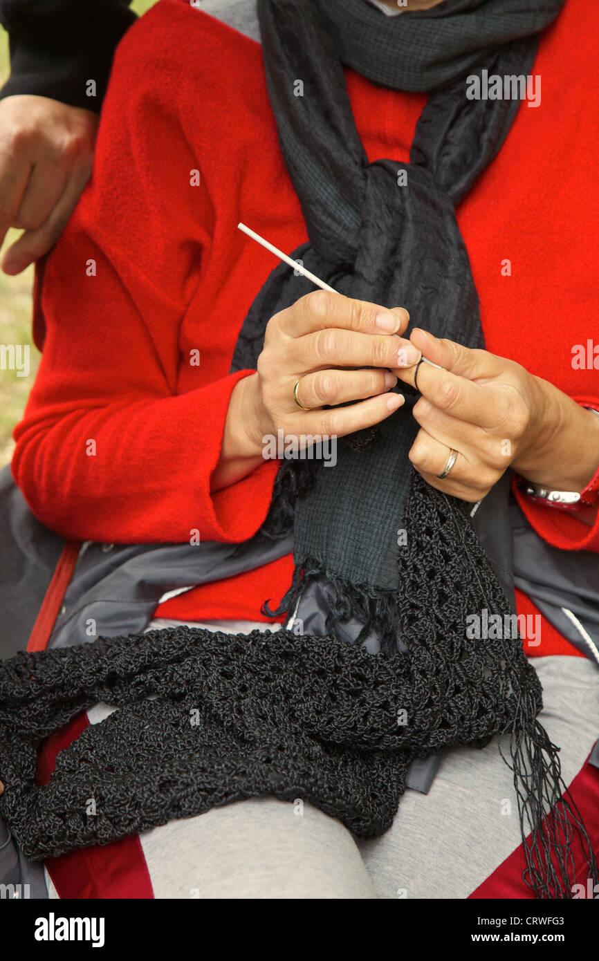 Woman making a black crochet work - Stock Image