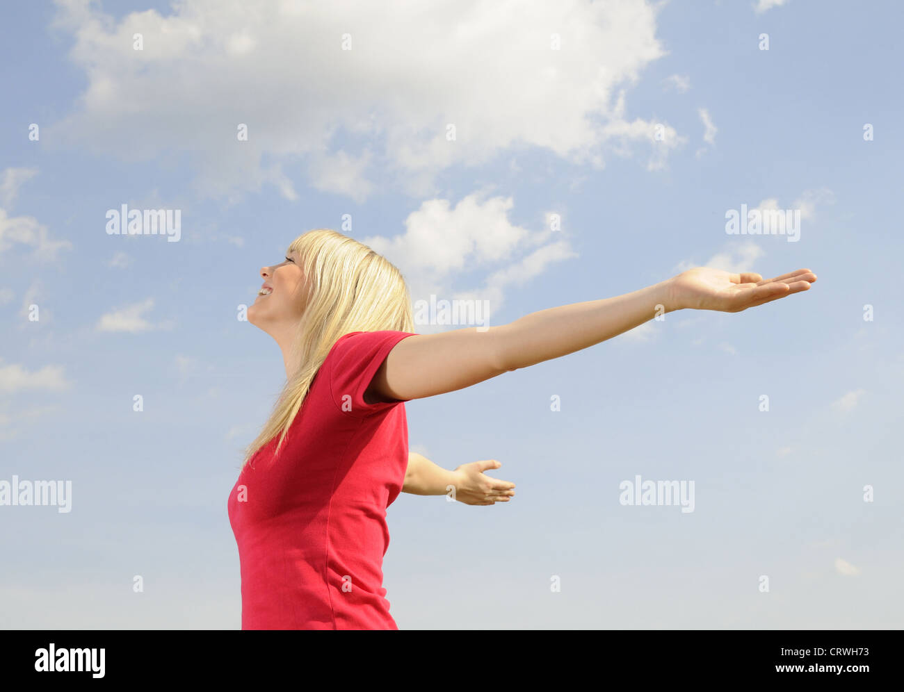 young woman spreads her arms - Stock Image