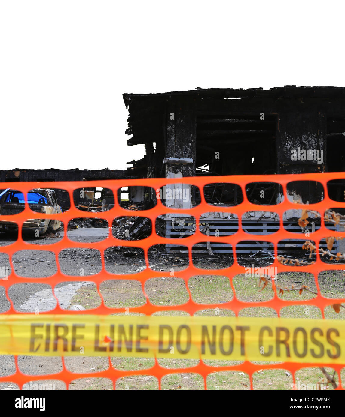 House burned in a fire (focus on the house) behind a orange fence, the background has been removed and is isolated - Stock Image