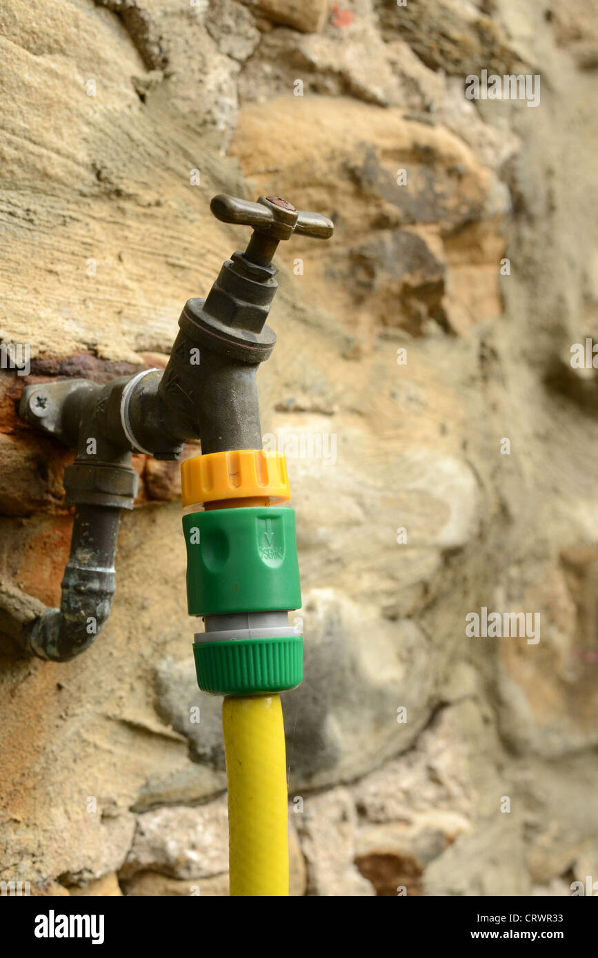 Garden tap with hose  fitted on an old stone cottage wall - Stock Image
