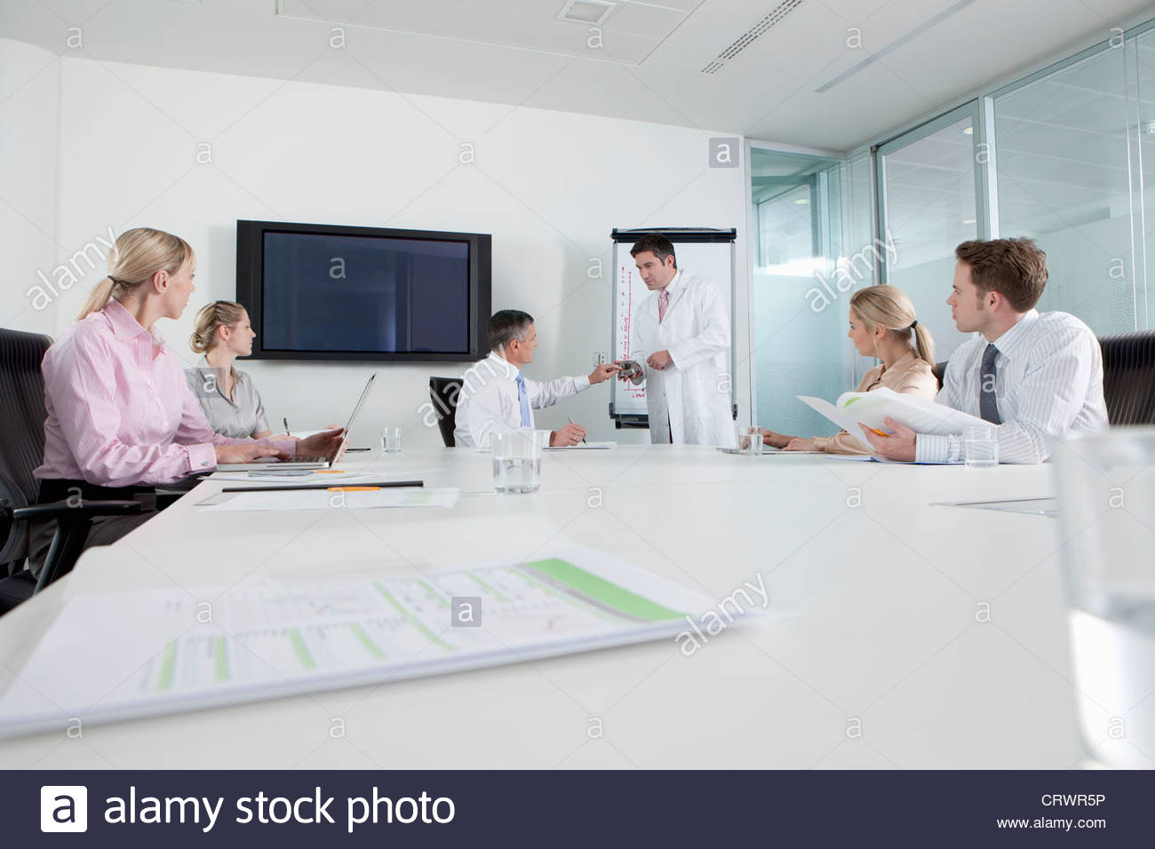 Engineer in lab coat leading meeting with business people in conference room - Stock Image