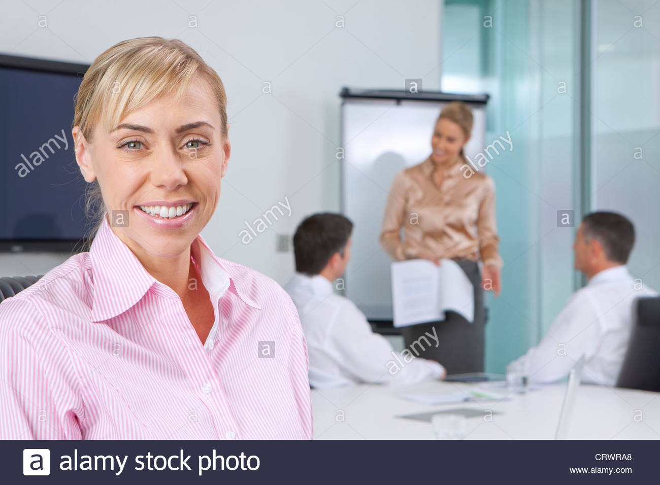 Portrait of smiling businesswoman in meeting in conference room - Stock Image