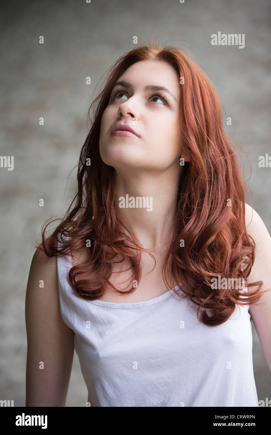 Portrait of a pensive young woman with red hair looking up - Stock Image