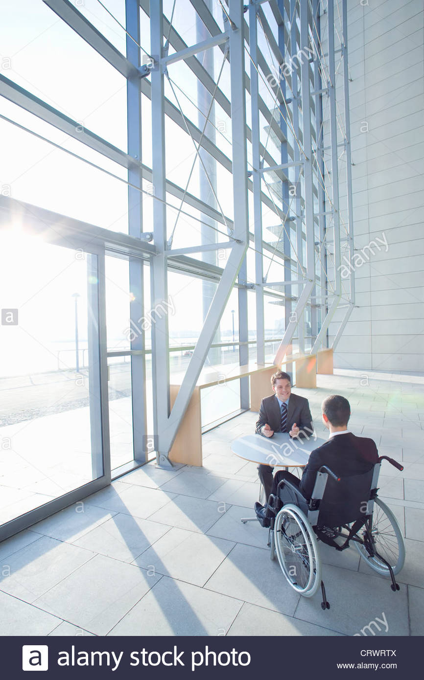 Businessman in wheelchair meeting with co-worker in modern lobby - Stock Image