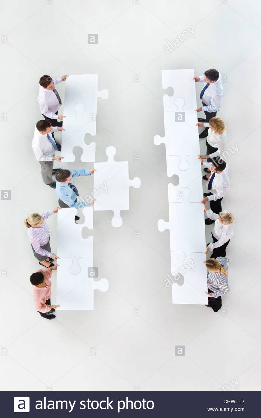 Business people standing face to face in rows and holding large jigsaw pieces Stock Photo