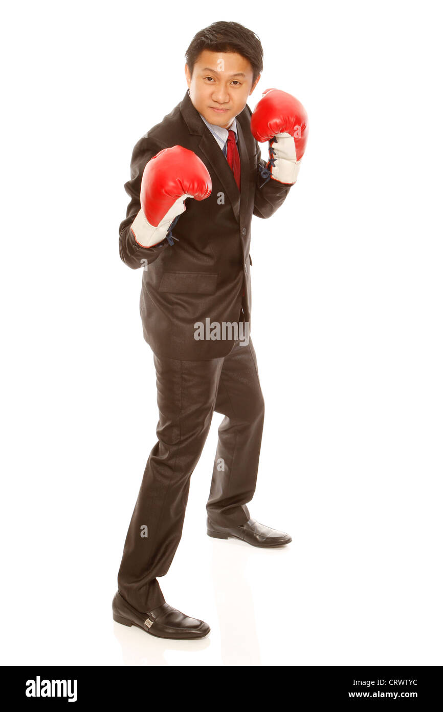 A businessman wearing boxing gloves in a fighting stance ...