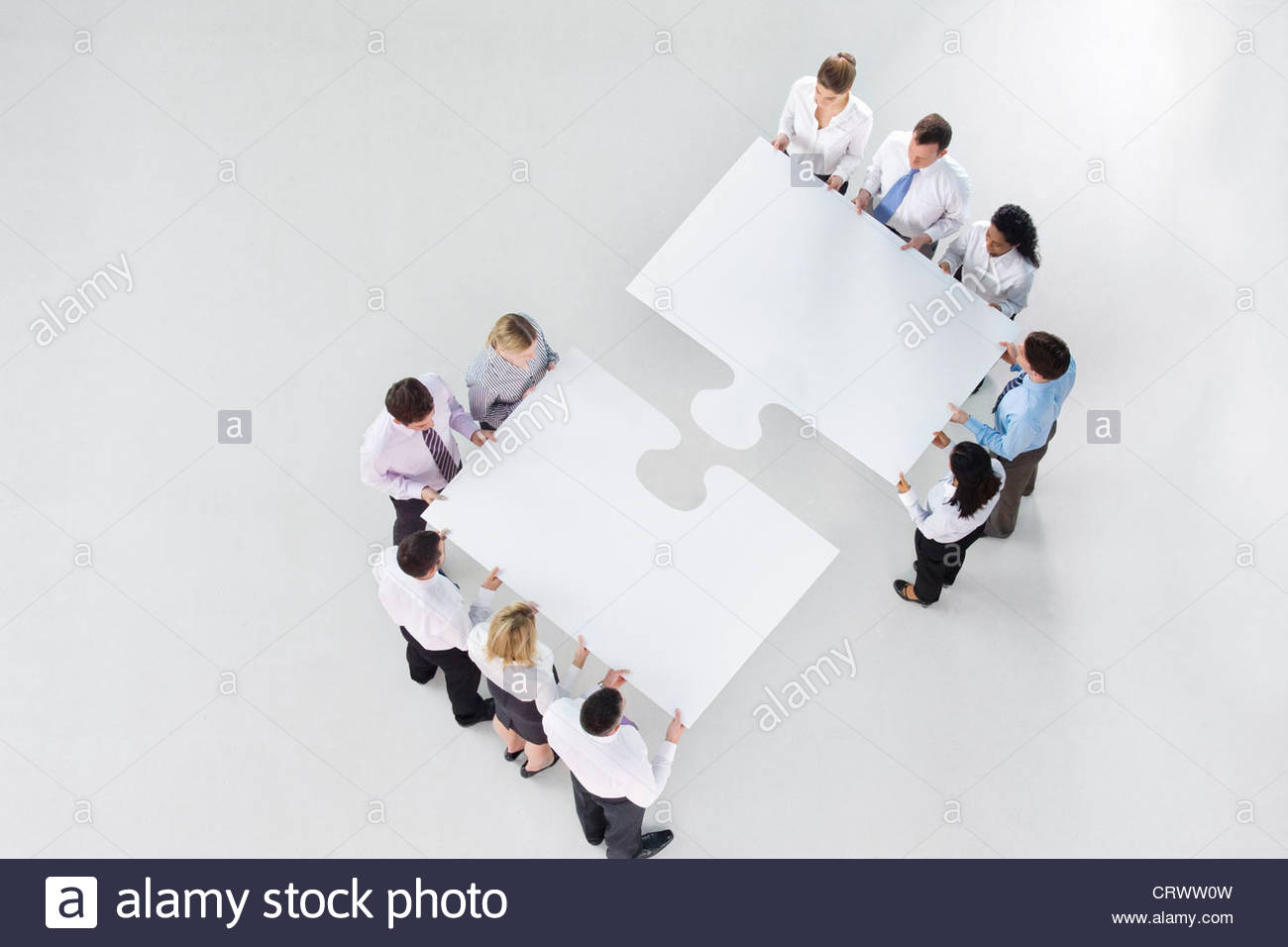 Two groups of business people connecting large jigsaw pieces - Stock Image