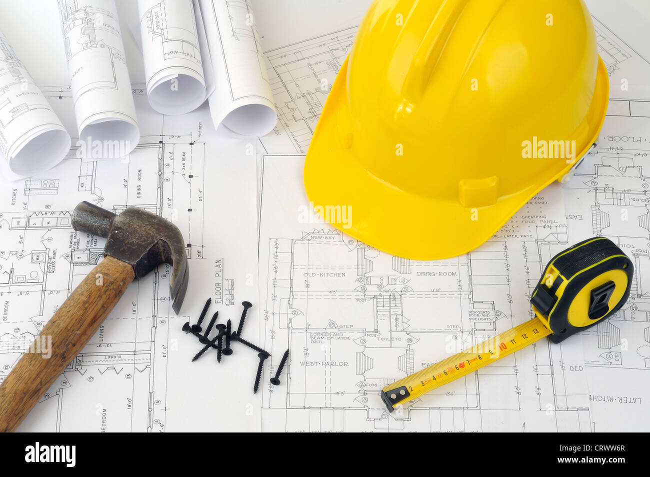 Yellow hard hat and heap of project drawings - Stock Image