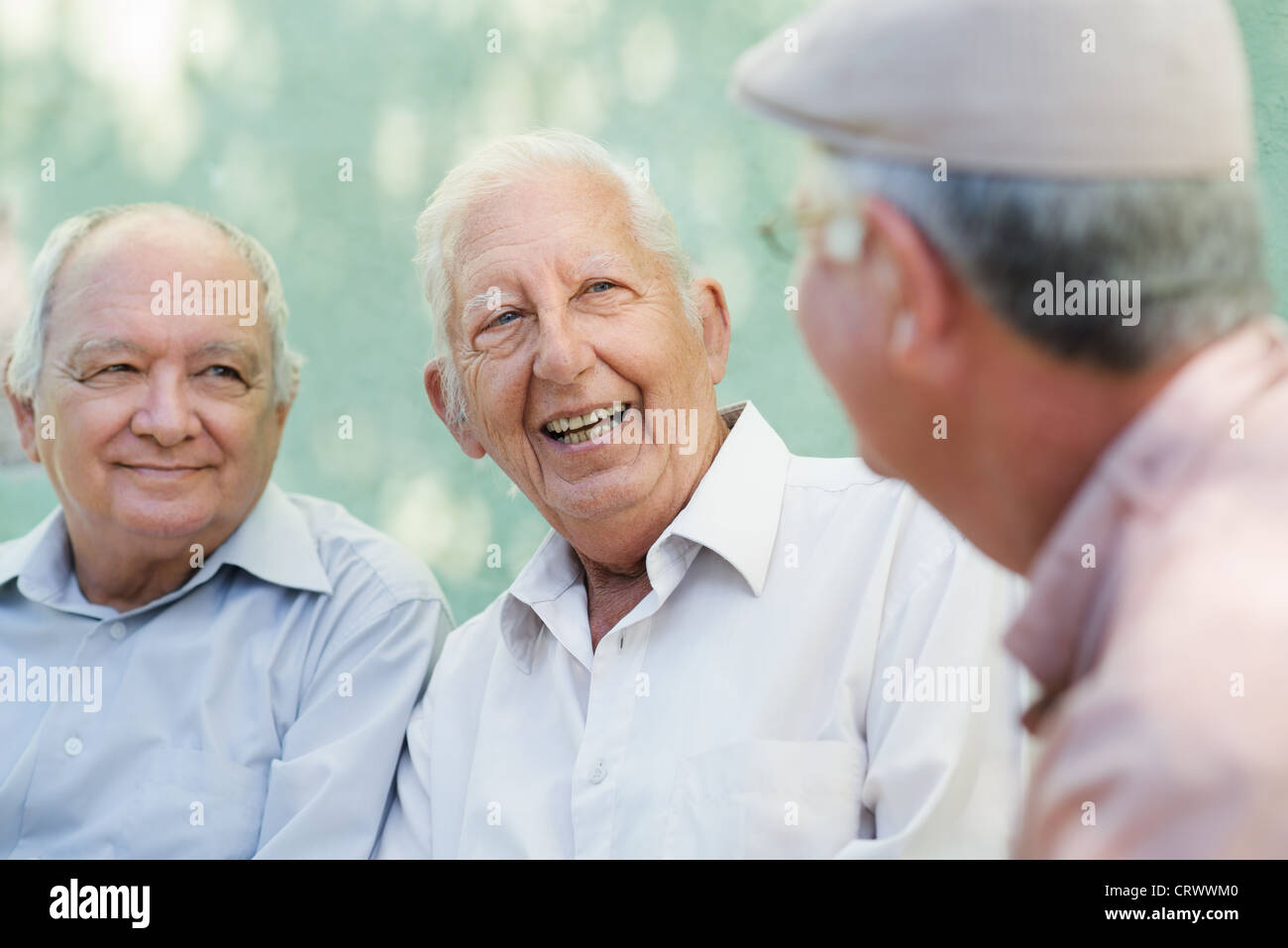 Active retirement, group of three old male friends talking and laughing on bench in public park - Stock Image