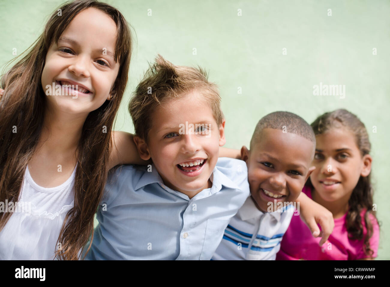 Group of happy children smiling, embracing and looking at camera. Copy space - Stock Image